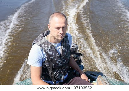 man in army fatigues moving boat