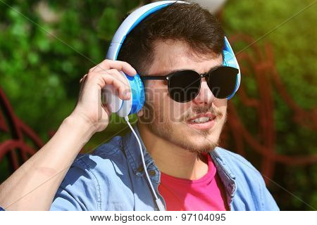 Man with headphones resting on bench in park