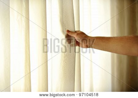 Man's Hand Pulling A Window Curtain