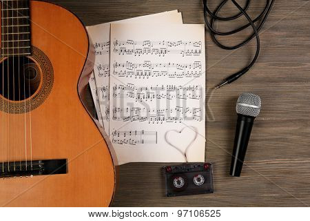 Music recording scene with classical guitar, music sheets, cassette and microphone on wooden table, closeup