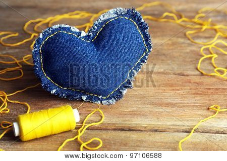 Denim heart and thread on wooden background