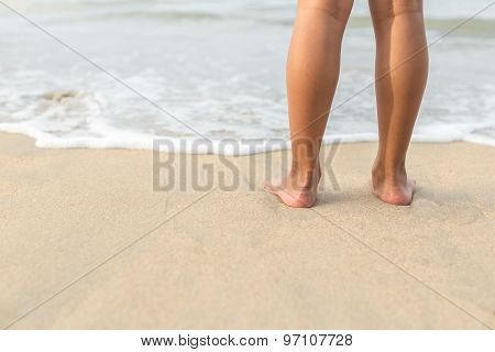 Legs Of Children Stand On The Beach