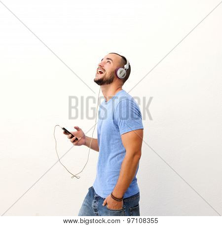 Happy Guy Walking With Cell Phone And Headphones