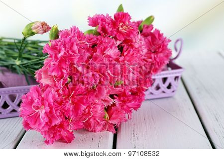 Beautiful bouquet of pink carnation on wooden table close up