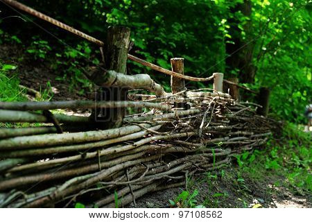 Wooden wicker fence over green trees background