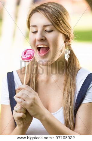 Funny Portrait Of Woman With Pigtails Looking At Lollipop