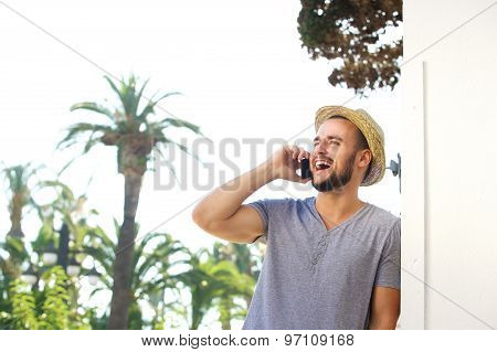 Young Man With Hat Listening To Mobile Phone And Laughing