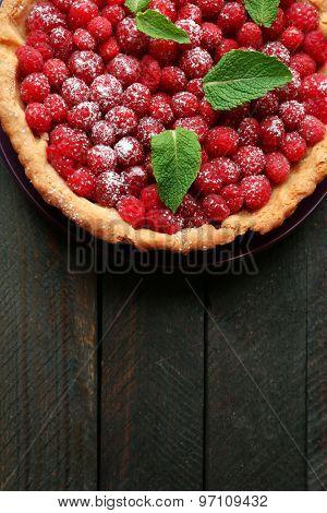 Tart with fresh raspberries, on wooden background