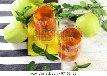 Glasses of apple juice with fruits and fresh mint on table close up