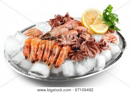 Seafood with lemon and ice on metal tray close up