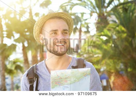 Happy Young Guy On Vacation Holding Map