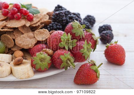 Breakfast - berries, fruit and muesli on white wooden