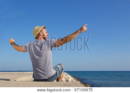 Man Sitting By The Sea With Arms Spread Open