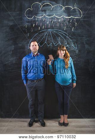Pregnant Woman And Man Covering Under Umbrella Drawn On Blackboard