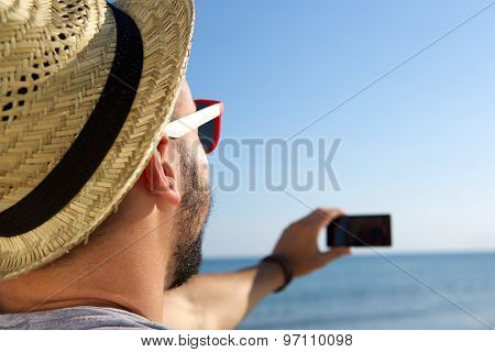 Young Man Taking A Selfie With Cell Phone At The Sea