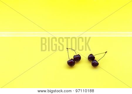 two couple sweet cherries on yellow background decotated with stripes