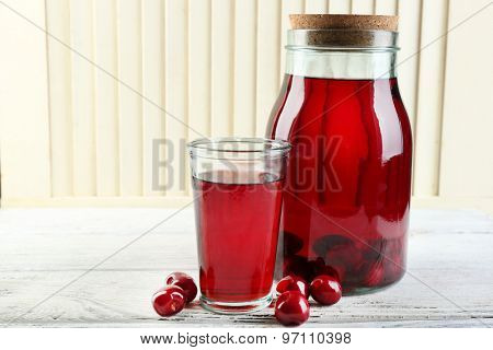 Sweet homemade cherry compote on table, on light background