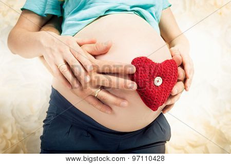 Caring And Loving Expectant Parents Holding Red Heart On Abdomen