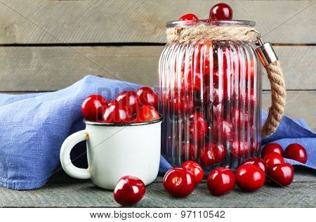 Sweet cherries in glass jar and mug, on wooden background