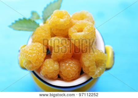 Yellow raspberries on turquoise table, closeup