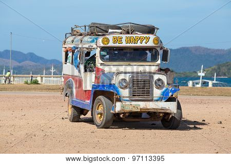 Jeepneys passing Philippines inexpensive bus service.