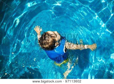 Young boy with inflatable swimming vest in the pool, has a happy smile.  Eye contact. Copy space