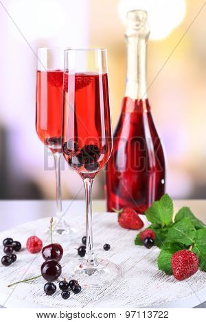 Glass of champagne with berries on light blurred background