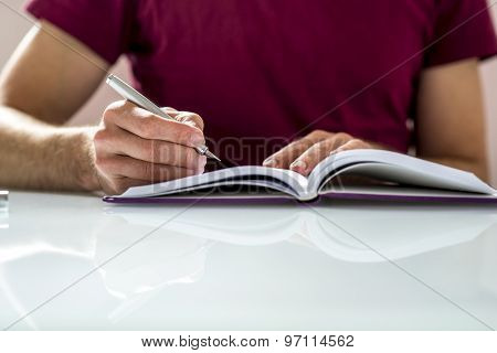 Close Up Of A Student Writing Notes Or Homework On A Clean Notebook