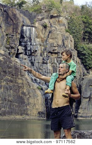 father and son making a trip to waterfall together, happy family on vacations, nature place