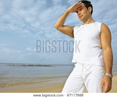 young brunette man on beach at sea smiling, gomosexual in white