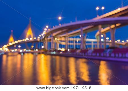 Abstract blurred bokeh city highway intersection and suspension bridge during twilight