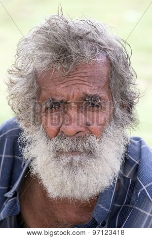 Sri Lankan beggar waits for alms on a street next to the bus station