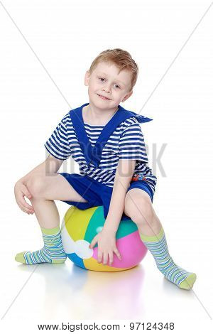 little boy is sitting on the ball