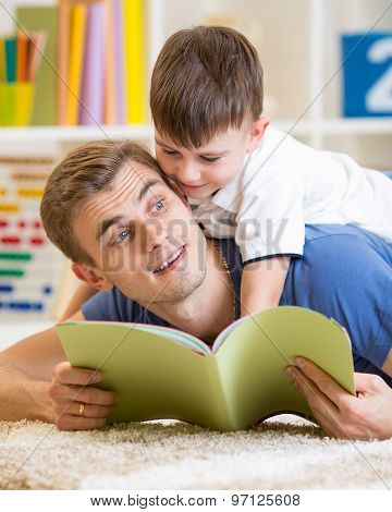 child boy and father read a book on floor at home