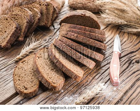 Sliced black bread on the old wooden plank.