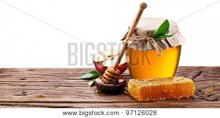 Glass can full of honey, apples  and on old wooden table. Clipping paths.