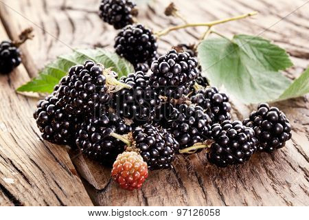 Blackberries with leaves on a old wooden table.