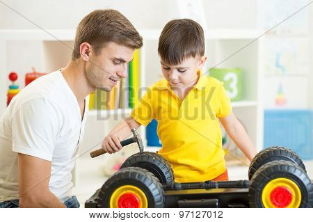 kid boy and his father repair toy lorry
