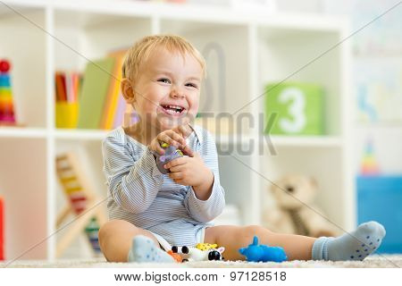 little child plays with toys animals
