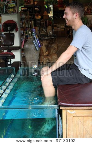 Boy Doing Feet Pedicure With Fishes