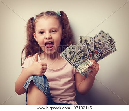 Happy Enjoying Kid Girl Holding Money And Showing Thumb Up Sign. Vintage Portrait