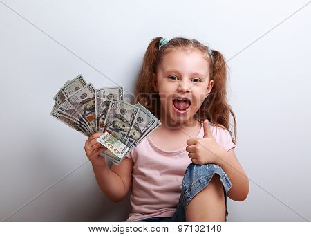 Happy Enjoying Kid Girl Holding Money And Showing Thumb Up Sign
