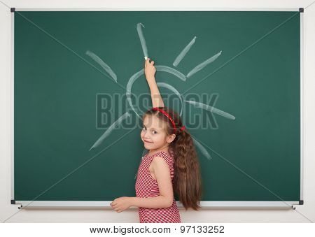 girl drawing sun by white chalk on school board