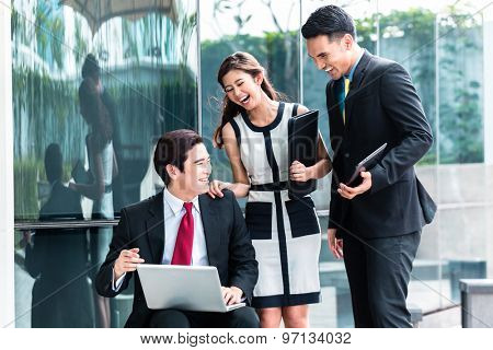 Asian business woman and men working outside on computer