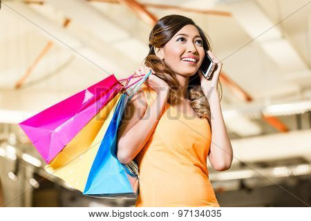 Asian young woman in fashion store or shop talking on phone telling her friends about the purchase she made