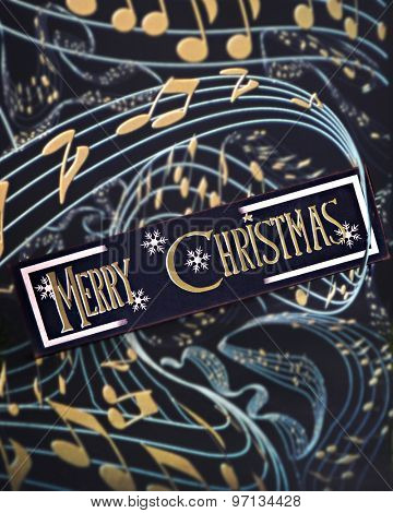 A Merry Christmas sign wrapped in pale blue staff with golden notes.  On a black background.