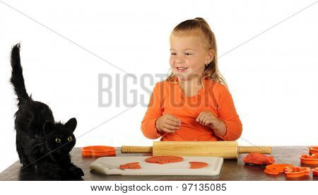 An adorable preschooler taking a break from cutting Halloween cookies out of modeling dough to look at an ugly black cat.