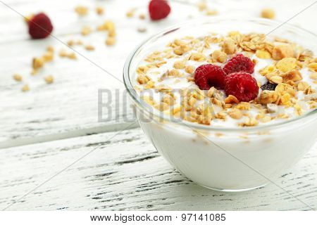 Muesli with yogurt in a bowl on the wooden background