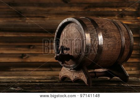 Wooden barrel with iron rings on brown wooden background