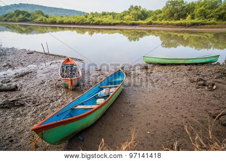 Three canoes on river bank in Goa, India